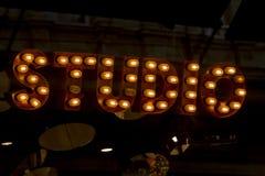 Zamyka w górę wizerunku znak z tekstem «studio «pisać z retro lampami wewnątrz sans serif typografia obraz royalty free