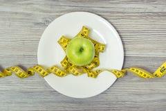 Zamyka w górę zasięrzutnej widok fotografii smakowity świeży zielony jabłko z taśmy miarą na drewnianym stole Odgórny widok na ta zdjęcie stock