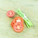 Zamyka w górę zielonego asparagusa i pokrajać pomidoru Zdjęcia Stock