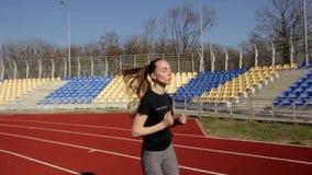 Zamyka w górę zwolnione tempo strzału sportowy atrakcyjny dysponowany młoda kobieta bieg jogging, plenerowy stadium trening na sł zdjęcie wideo