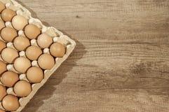 Zamyka w górę jajek w kartonu pakunku na drewnianym stole dla piec Zdjęcie Stock
