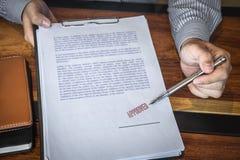 Zamyka w g?r? r?k wskazuje podpisywa? biznesmen i stempluje na papierowym dokumencie zatwierdza? biznesowej inwestycji kontraktac fotografia stock