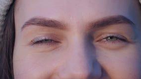 Zamyka w g?r? portreta zieleni oczy m?oda atrakcyjna u?miechni?ta kobieta kt?ra otwiera ona oczy, patrzeje kamer? i szcz??liwie zdjęcie wideo