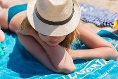 Zamykająca blondynki dziewczyna w kapeluszu na plaży Obraz Royalty Free