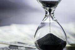 Zamykający up piasek spada w sandglass lub hourglass na dolarze amerykańskim fotografia royalty free