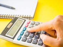 Zamykający w górę kobiety ręki używać kalkulatora z czarnym piórem fotografia royalty free