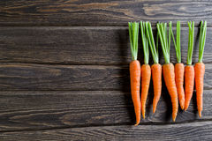 Zanahoria fresca en un fondo de madera oscuro foto de archivo