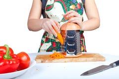 Zanahoria grating de la mujer aislada en blanco foto de archivo