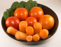Zanahoria, tomate y espinaca en una placa negra, fondo blanco Foto de archivo