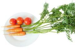 Zanahoria y tomate en la placa blanca Fotografía de archivo