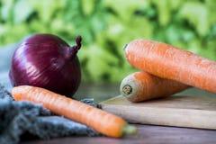 Zanahorias ascendentes cercanas y unión roja en tabla de cortar de madera contra fondo verde de la falta de definición de la hoja imagen de archivo libre de regalías