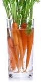 Zanahorias con las hojas que se colocan en un vidrio de agua. Fotos de archivo libres de regalías