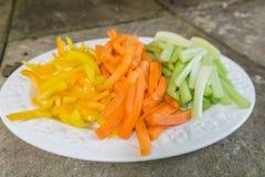Zanahorias cortadas apio y pimientas en una placa Imagenes de archivo