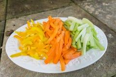 Zanahorias cortadas apio y pimientas en una placa Imágenes de archivo libres de regalías