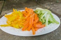 Zanahorias cortadas apio y pimientas en una placa Fotografía de archivo