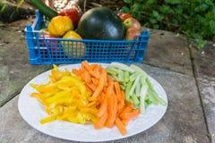 Zanahorias cortadas apio y pimientas en una placa Imagen de archivo