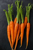 Zanahorias crudas en fondo negro imagen de archivo libre de regalías