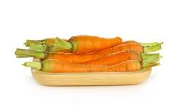 Zanahorias de bebé en placa de madera en el fondo blanco foto de archivo libre de regalías
