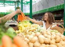 Zanahorias de compra de la mujer joven en el mercado del ultramarinos Imágenes de archivo libres de regalías
