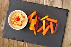 Zanahorias del arco iris del bebé con hummus en el servidor de la pizarra Imágenes de archivo libres de regalías
