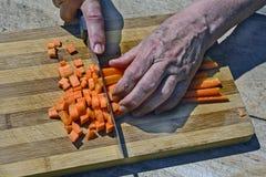 Zanahorias del corte con el cuchillo Fotografía de archivo