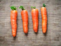 Zanahorias en fondo marrón de la tela Imagen de archivo libre de regalías
