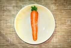 Zanahorias en plato en fondo marrón de la tela Fotos de archivo libres de regalías