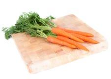 Zanahorias en tarjeta de madera Imagenes de archivo
