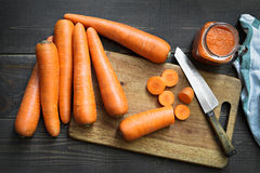 Zanahorias frescas con el jugo de zanahorias con la tabla de cortar y el cuchillo en fondo de madera Foto de archivo