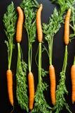 Zanahorias frescas en una tabla de madera negra Fotografía de archivo