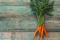 Zanahorias frescas en viejos tableros con la pintura verde lamentable Imagenes de archivo