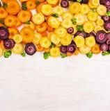 Zanahorias multicoloras del corte en de madera blanco Imagen de archivo