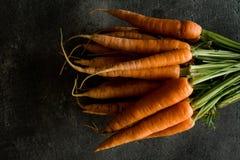 Zanahorias orgánicas de Nantes en fondo oscuro rústico Superfoo fresco imagen de archivo libre de regalías