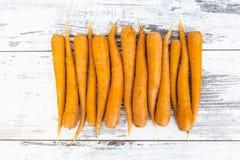 Zanahorias orgánicas en la tabla de madera Foto de archivo