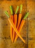 Zanahorias peladas en un vector de madera rústico Fotos de archivo