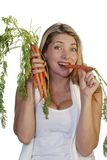 Zanahorias penetrantes de la mujer atractiva Fotografía de archivo libre de regalías