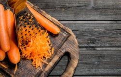 Zanahorias ralladas en una tabla de cortar con un rallador imagen de archivo libre de regalías