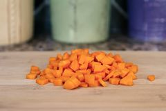 Zanahorias recientemente cortadas en cuadritos en una tabla de cortar de madera imagenes de archivo