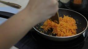 Zanahorias tajadas fritas en el aceite vegetal en la cacerola Primer metrajes