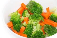 Zanahorias y bróculi frescos en un cuenco blanco Fotos de archivo libres de regalías