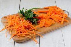 Zanahorias y perejil cortados en una tabla de cortar imagen de archivo