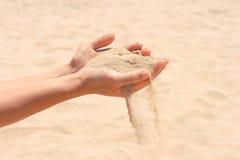 Zand dat handen doorneemt Stock Afbeeldingen