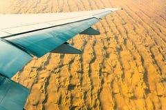 Zand in de woestijn onder de vleugel van een vliegtuig Verbazende mening van het venster van het vliegtuig tijdens de vlucht royalty-vrije stock foto's