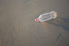 Zand en fles op een strand Stock Foto's