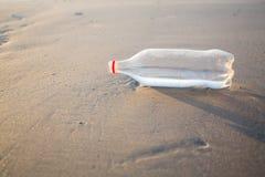 Zand en fles op een strand Stock Fotografie