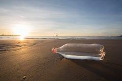 Zand en fles op een strand Stock Afbeelding