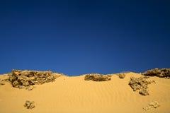 Zand met rotsen onder donkerblauwe hemel Royalty-vrije Stock Foto