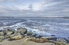 Zand, rotsen, mudflats en hemel royalty-vrije stock fotografie