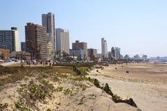 Zandduinen en Mensen tegen Stadshorizon Royalty-vrije Stock Afbeeldingen
