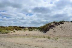 Zandduinen met gras op strand van DE Koog Texel in Nederland met bewolkte hemel stock fotografie